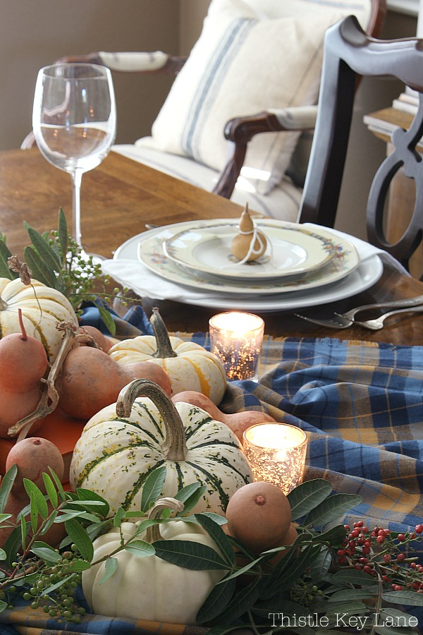 Easy Thanksgiving Tablescape Using Gourds And Plaid - adding candles for a cozy meal.