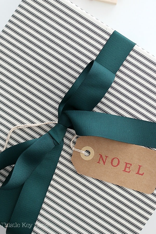 Black ticking stripe box with green ribbon and Noel gift tag.