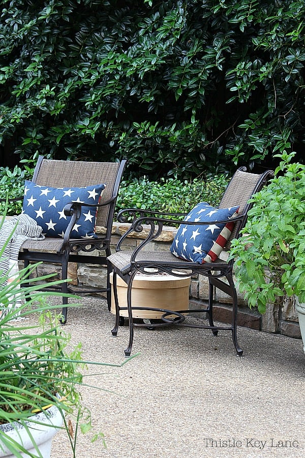 Patio chairs with navy and white pillows surrounded by plants.