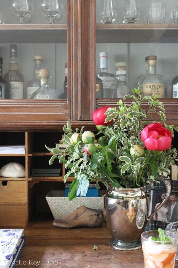 Vintage secretary with glass cabinet for liquor storage.