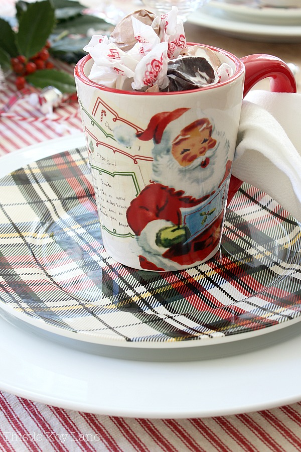 Santa cup with candy on a plaid plate.