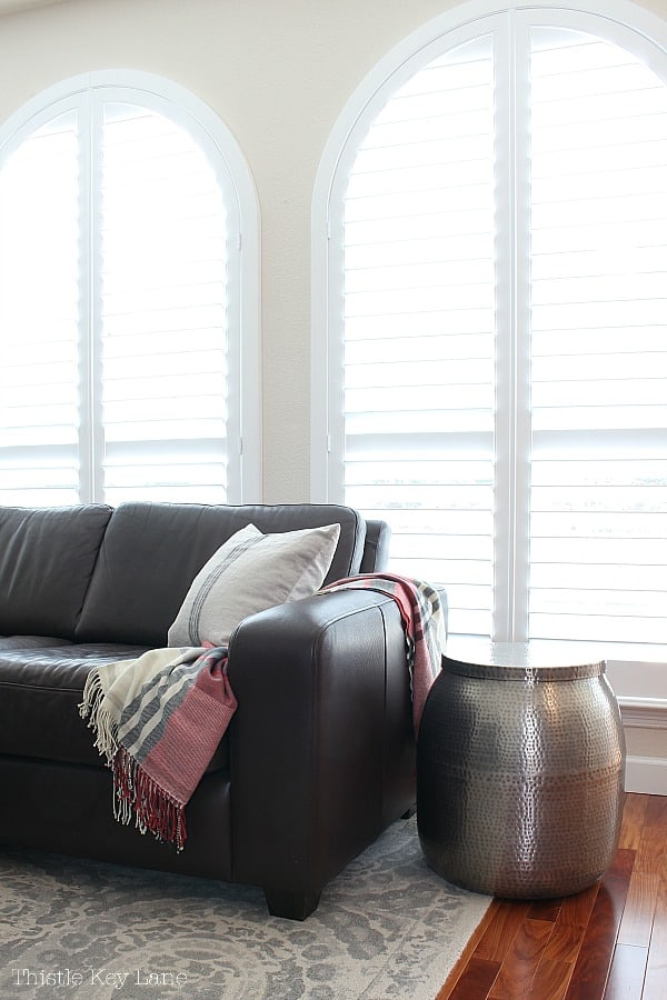 Winter Decorating Family Room Tour - brown leather sofa with white shutters in the background.