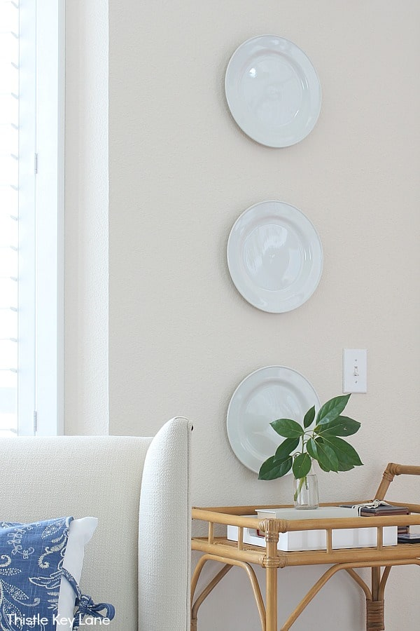 White plates on wall next to windows and a rattan bar cart.