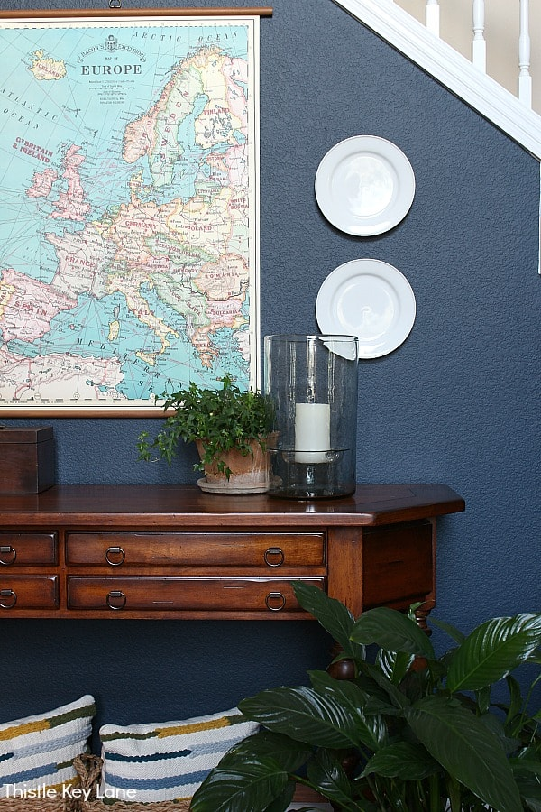 White plates on a navy wall with map. Ideas For Decorating With Plates