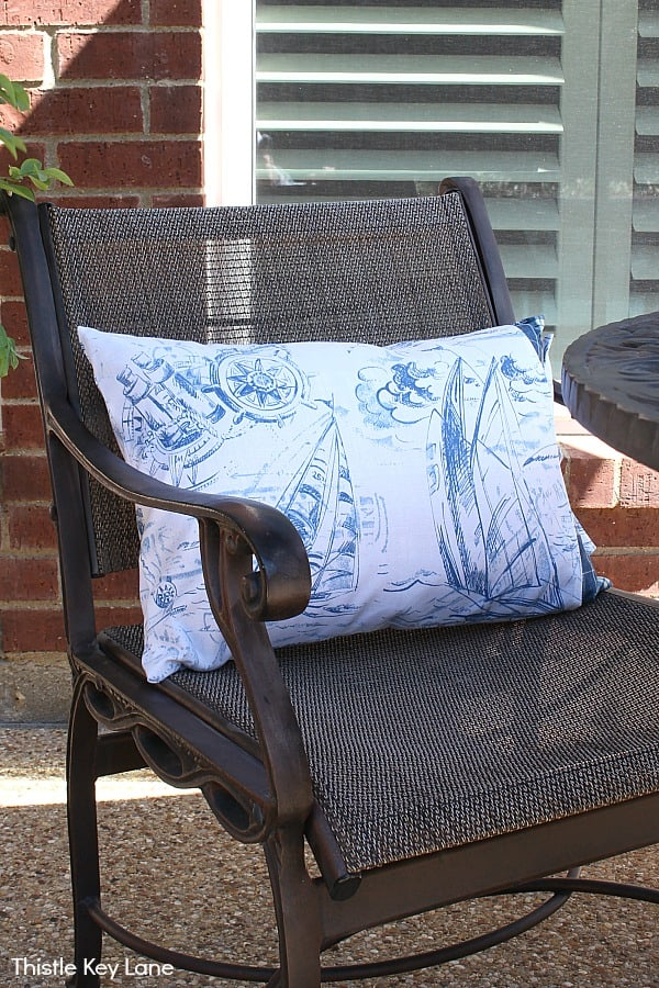 Outdoor pillow cover with nautical pattern on patio chair.