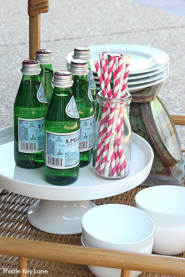 Cake plate holding drinks and straws on a bar cart.