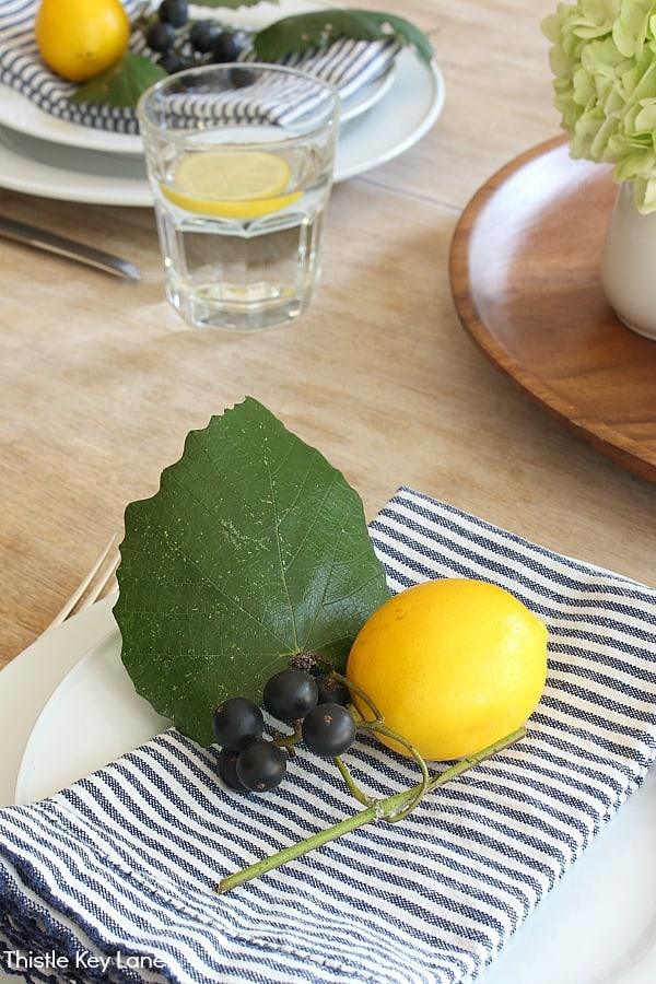 Lemon and wild grapes on a striped napkin. Summer Lemon Tablescape And A Free Printable.