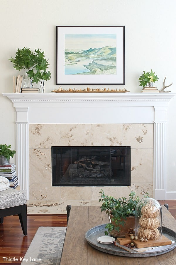 White mantel with watercolor painting with greenery on each side.