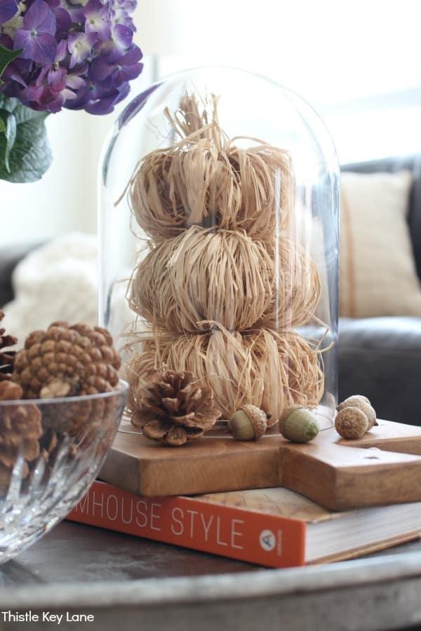 Raffia pumpkins stacked in a glass cloche -