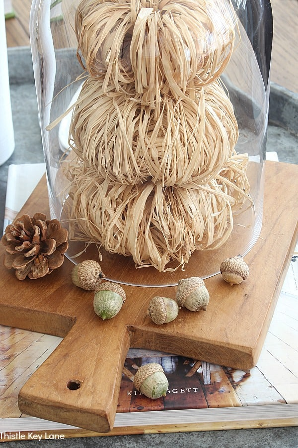 Acorns and a pinecone on a cutting board with raffia pumpkins.