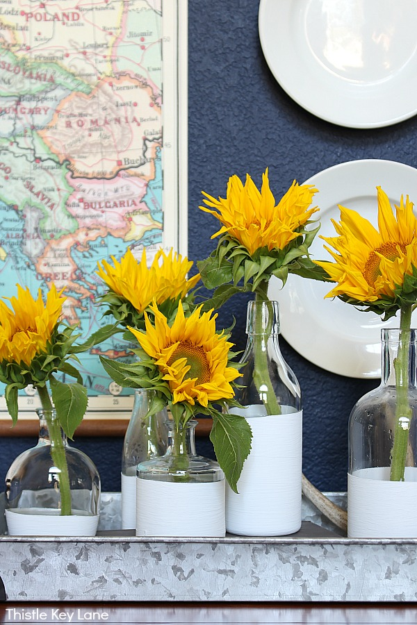 Up close sunflowers in five white vases navy wall with map and plates.