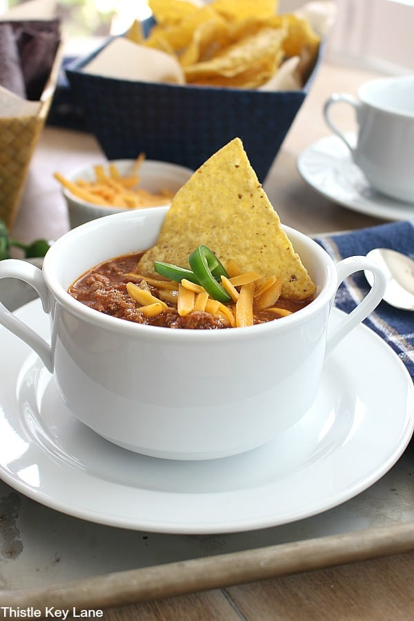 White bowl of chili with cheese, tortilla chip and jalapeno slices. Best Chili Recipe.