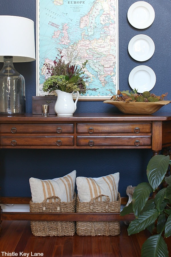 Entry table with navy wall background and vintage looking map.