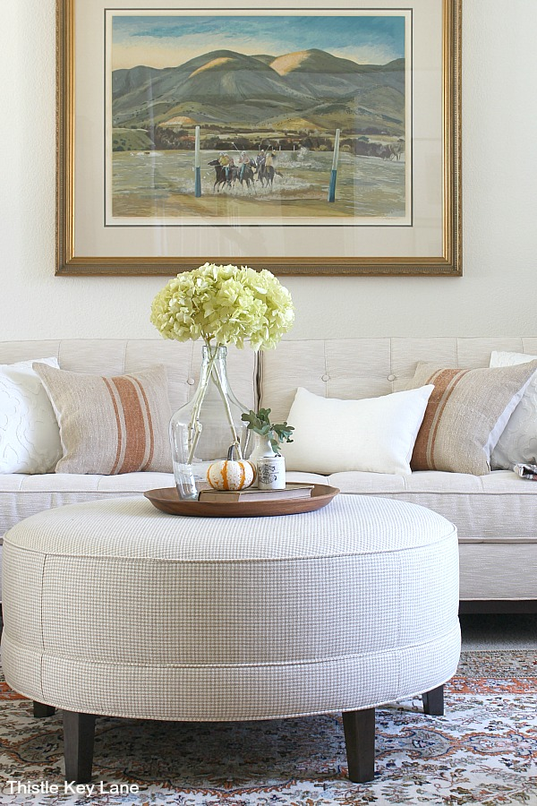 Neutral color sofa and round ottoman with tray.