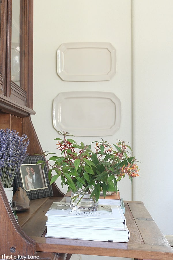 Side view of a secretary desk with flowers on books and ironstone platters on wall. Fall Home Tour With Subtle Colors