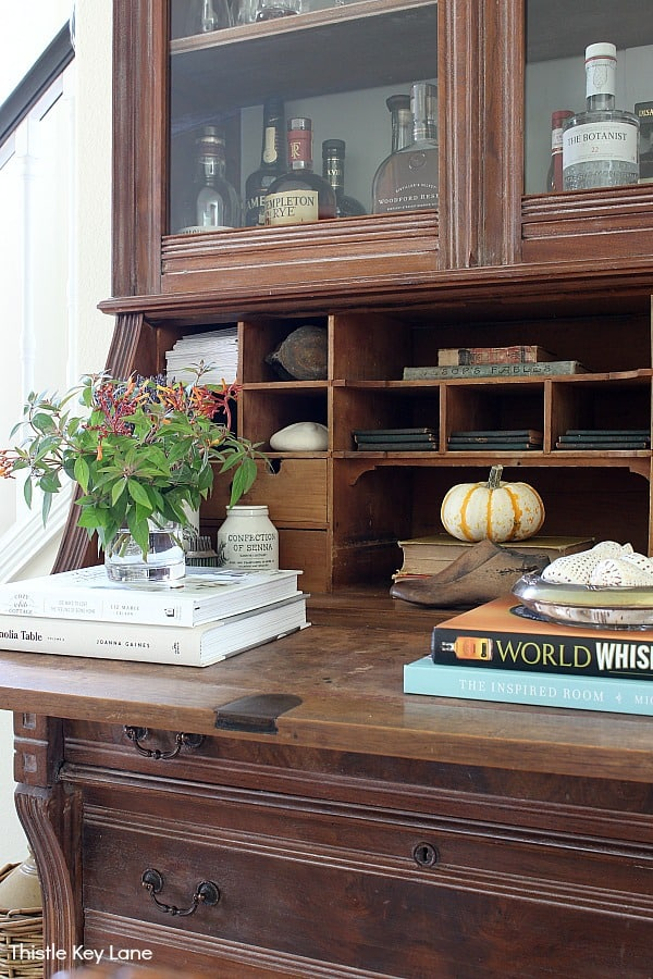 Secretary desk with books, flowers and a pumpkin.