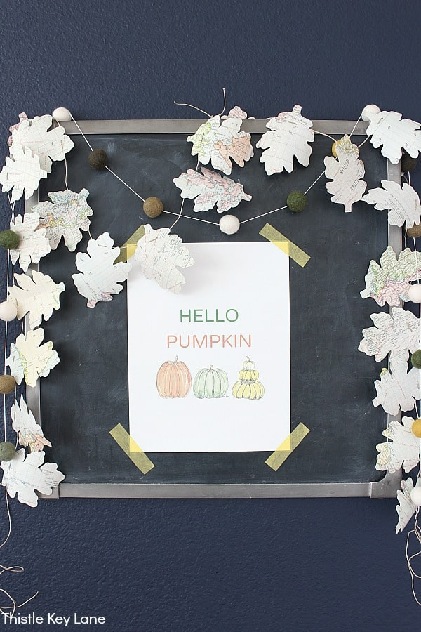 Chalkboard display with leaf garland and a Hello Pumpkin print in the center. DIY Map Leaf Garland And Fall Printables.