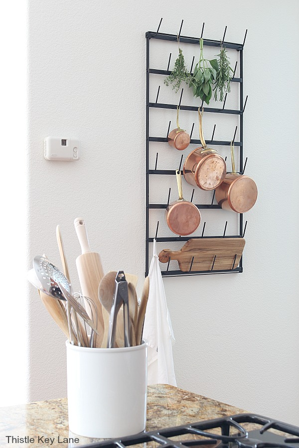 View of black metal wall rack with copper pots - Repurposing A Cup Rack For Pots & Pans.