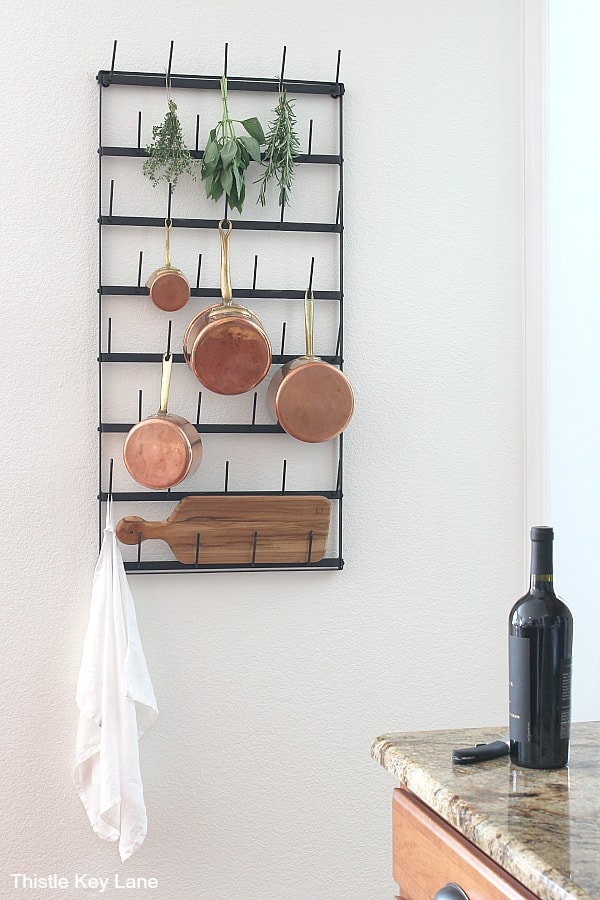Cup rack used as a pot rack on white wall in kitchen.