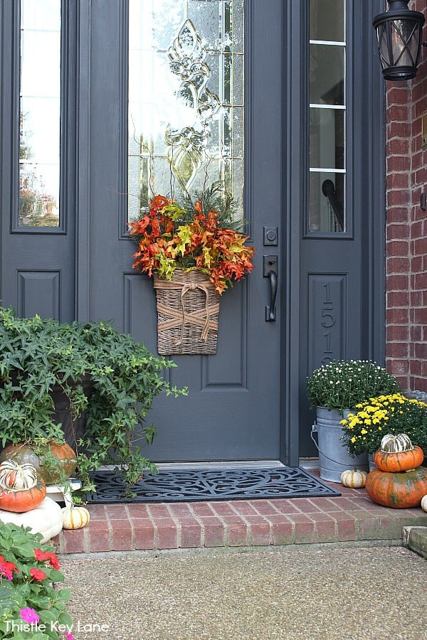 Small porch with pumpkins, mums and a fall door arrangement in a basket.