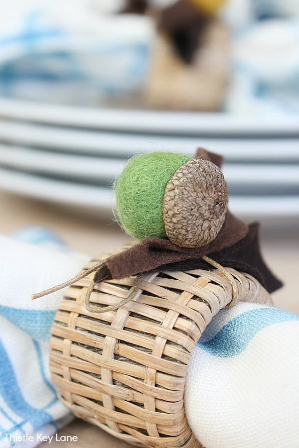 Green felt acorn and felt leaves tied on a woven napkin ring.