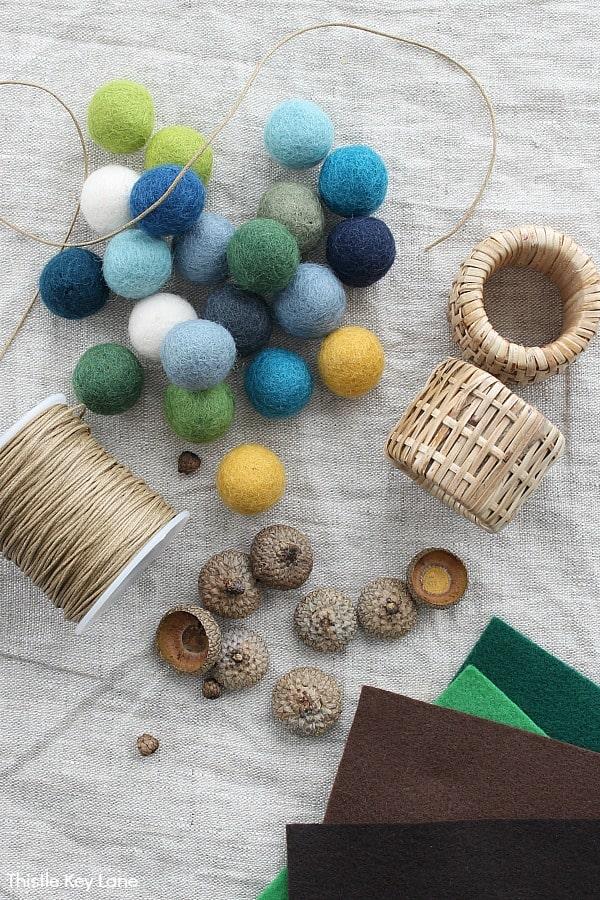Wool felt pompoms, acorn caps, cotton wax string, napkin rings and colored felt. DIY Felt Acorn Napkin Rings.