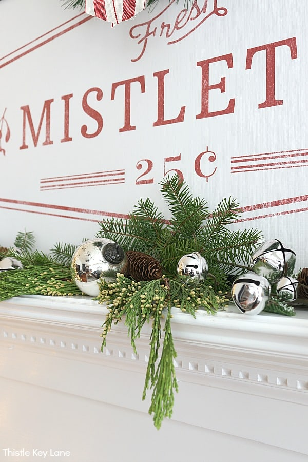 Fresh and faux greenery on the mantel with mercury glass and silver jingle bells.