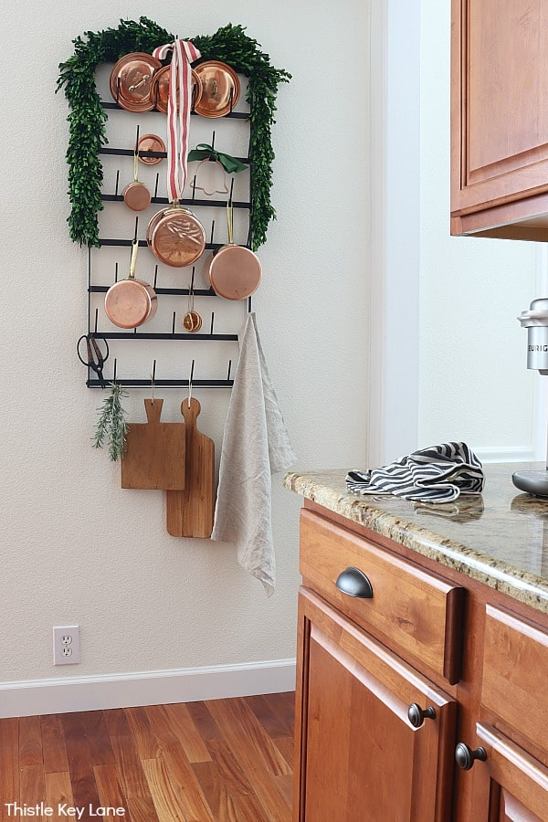Pot rack decorated with holiday greenery.