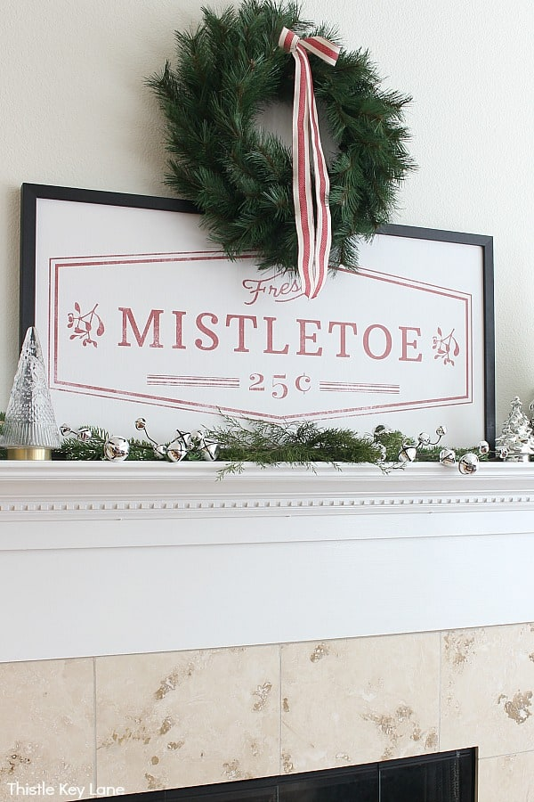 Pine wreath with red and white bow above a vintage mistletoe sign. Cozy Christmas Mantel In Red And White.