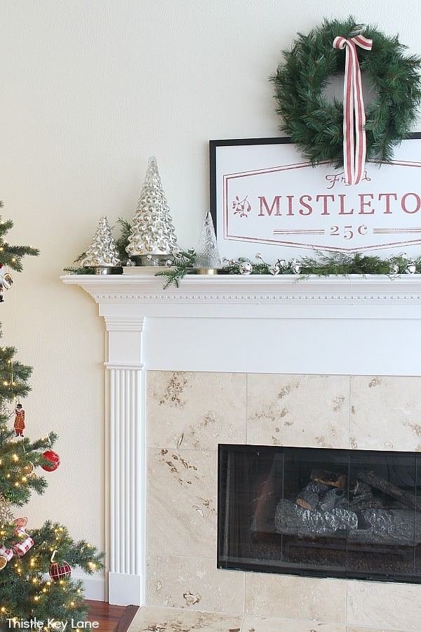 Red and white accents in a vintage sign over a mantel. Cozy Christmas Mantel In Red And White.