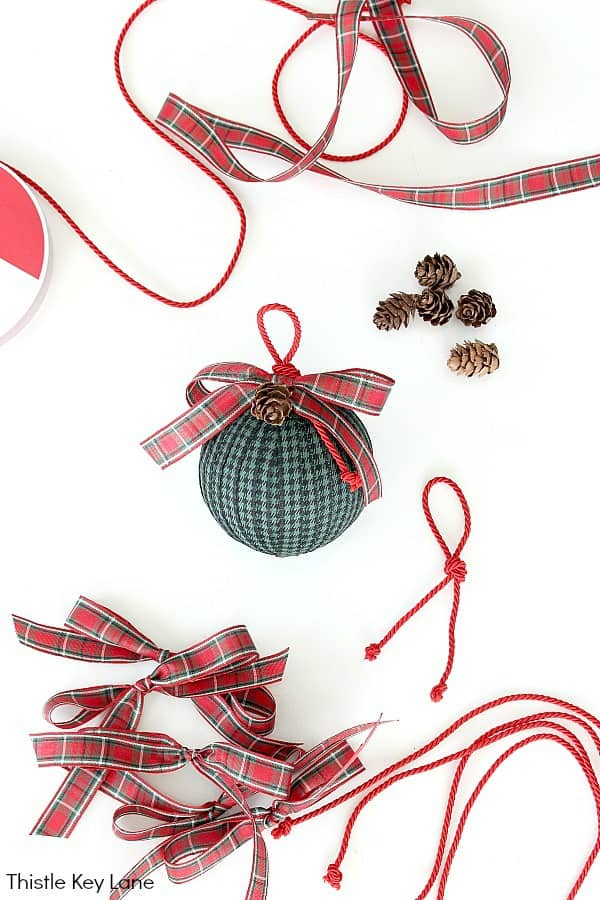 Completed Ornament In Center With Bows and Corning Supplies. How To Make Ribbon And Ticking Christmas Ornaments.