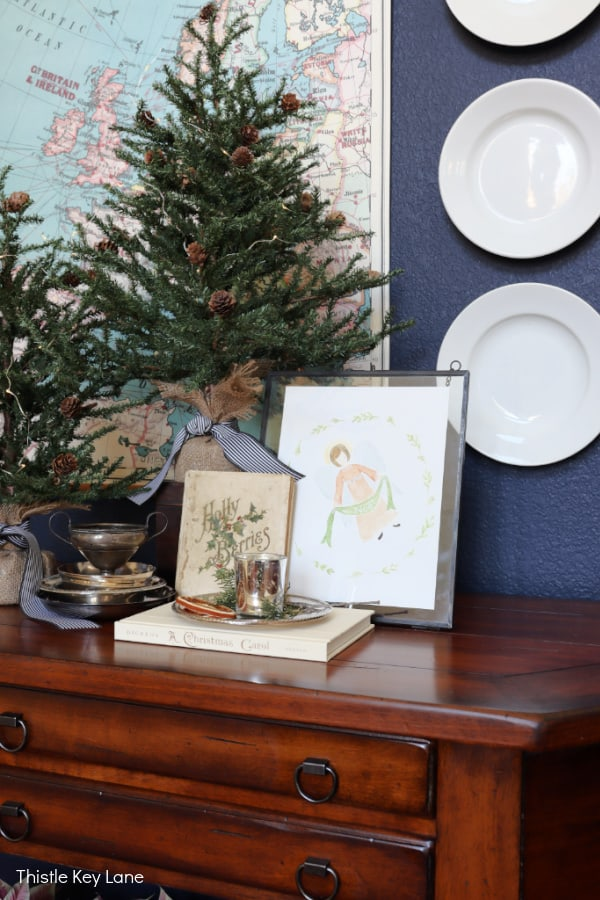 Entry table with mini trees, books and an angel watercolor. Holiday Wishes And An Angel Printable.
