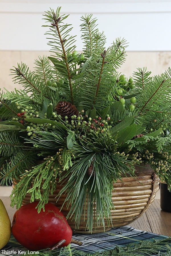 Evergreen arrangement in a bamboo bowl. Evergreen Christmas Centerpiece And Tablescape.