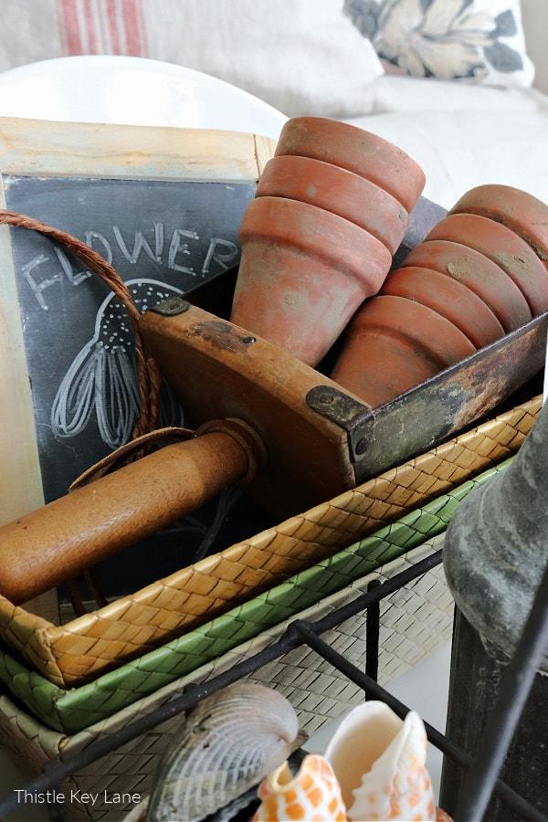 Antique wooden and metal scoop holding terra-cotta pots.