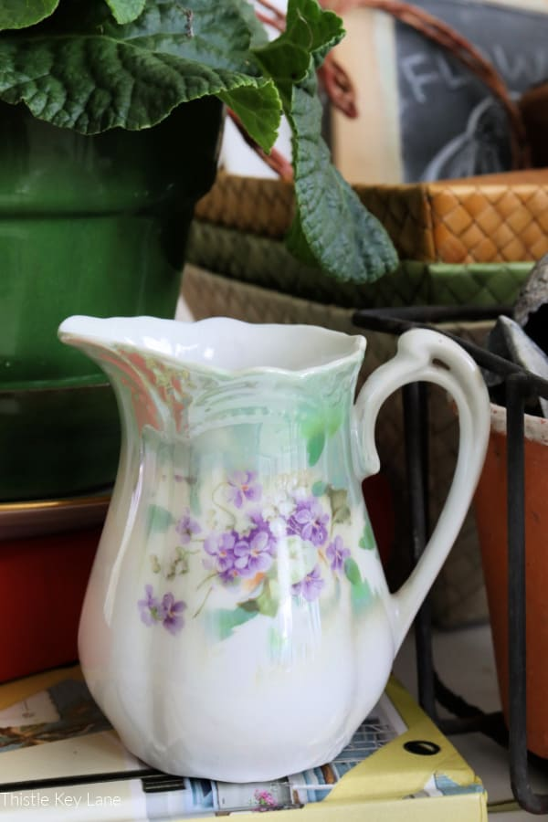 Winter botanical Inspired vignette. Small pitcher with purple violet pattern.