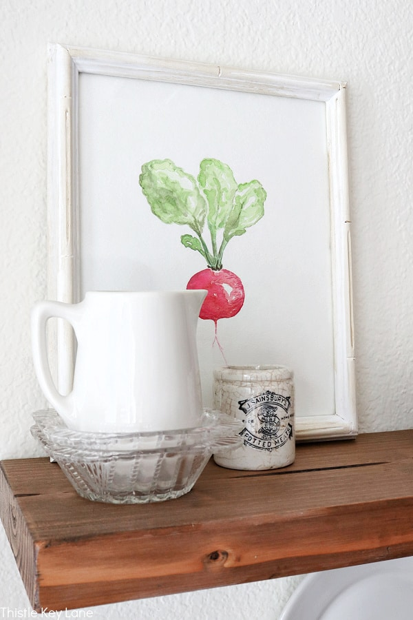 Ironstone creamer in a glass bowl with radish watercolor. Easy Ways To Style Floating Shelves.