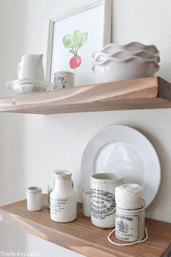 Ironstone jars and a plate on a floating shelf. Easy Ways To Style Floating Shelves.