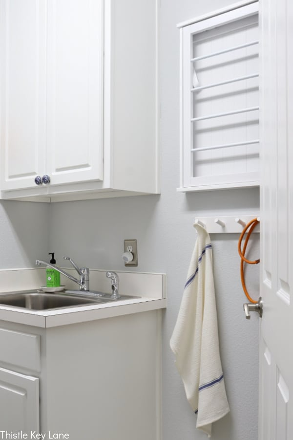 Laundry Room Organizing Ideas - with storage cabinets and sink and wall racks.