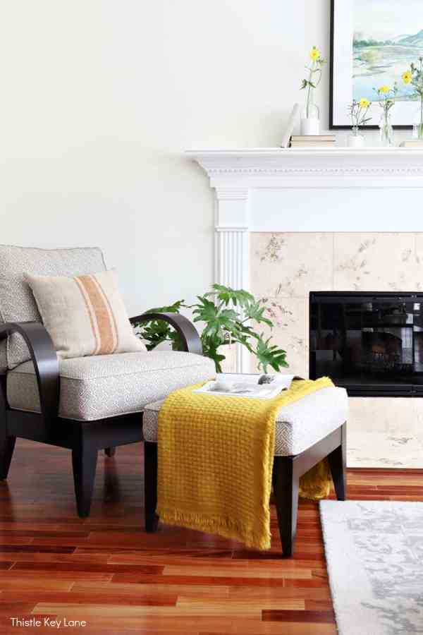 Neutral color arm chair and ottoman in front of the fireplace. Spring Mantel With Flowers And Bottle Vases.