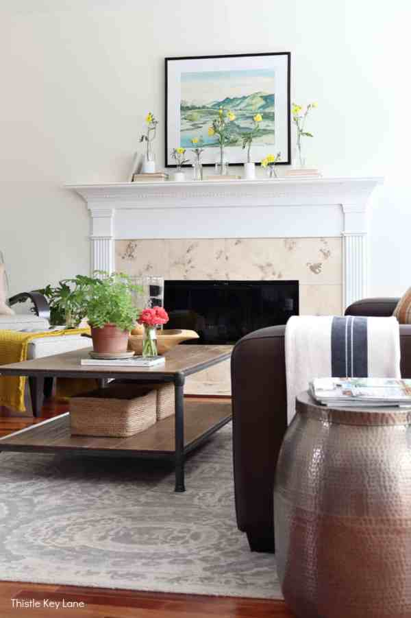 Spring family room with coffee table and mantel decorated with flowers. Spring Mantel With Flowers And Bottle Vases.