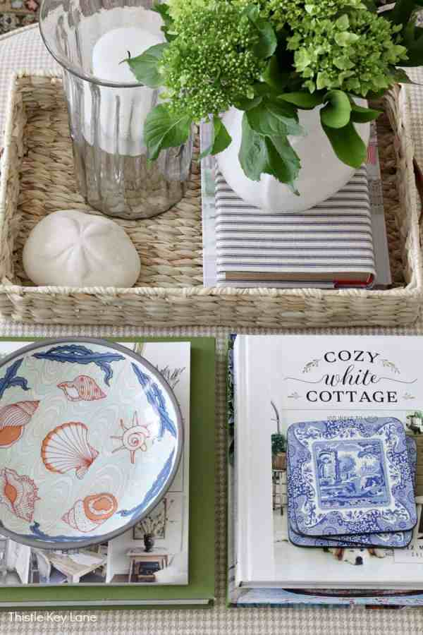 Flat lay of a tray, books and blue accessories on an ottoman. Decorating With Hints Of Blue.