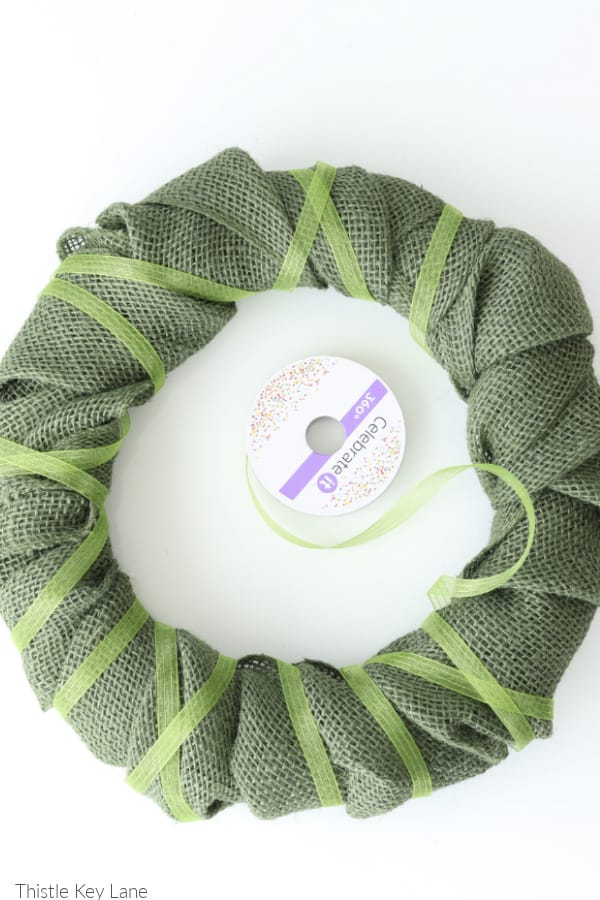 Light green ribbon wrapped around burlap wreath. Spring Burlap And Carrot Wreath.