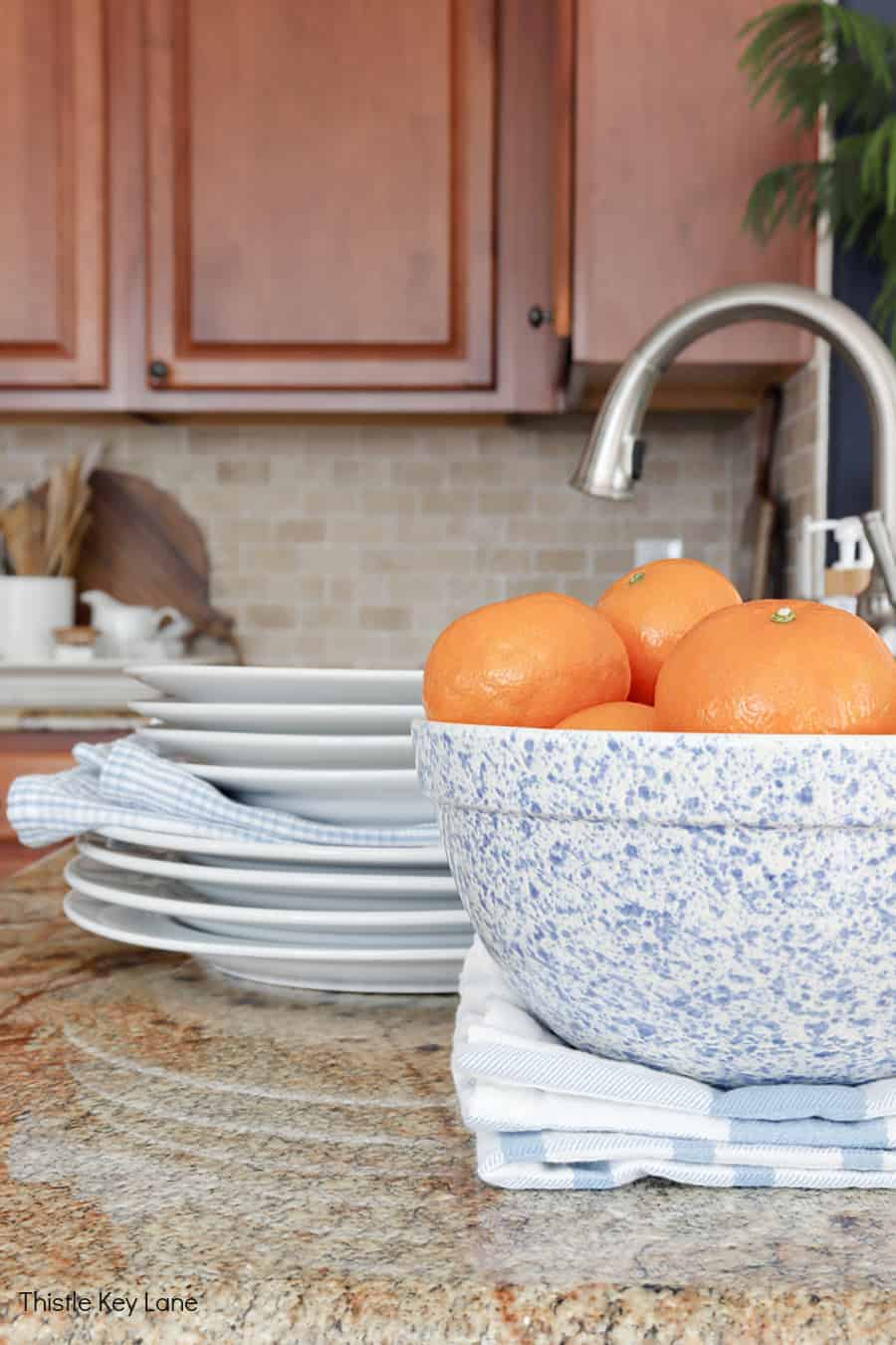 Bowl of oranges and white dishes sitting on a counter - Using Trays To Control Kitchen Clutter.