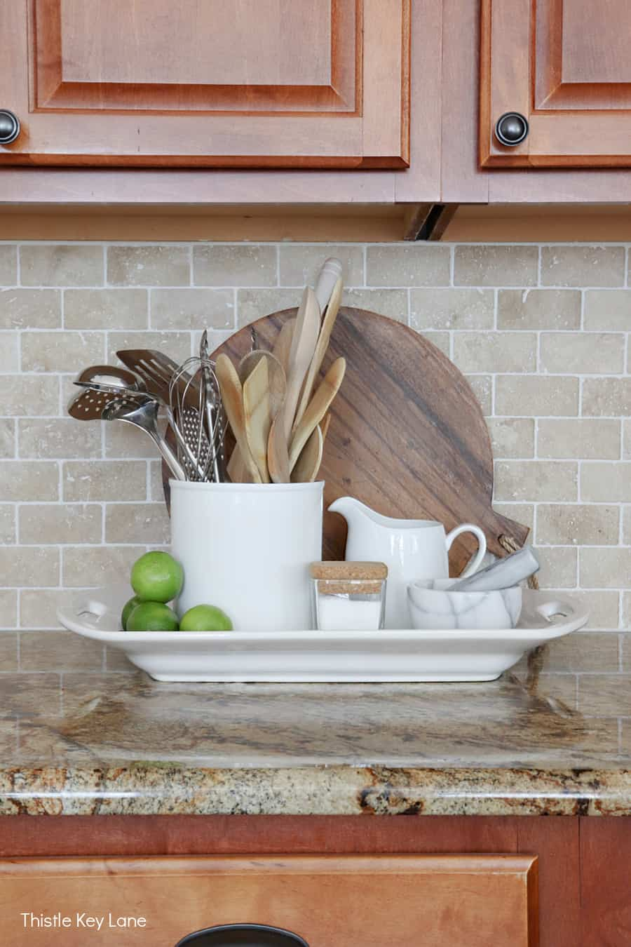 Ironstone tray holding utensils, cooking supplies, round cutting board - Using Trays To Control Kitchen Clutter.