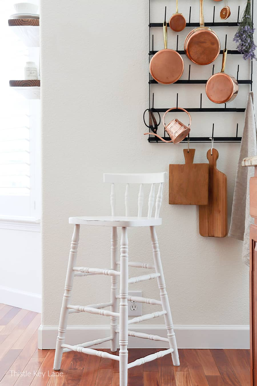 White painted chair next to wall pot rack. Updating A Vintage Chair With Paint.