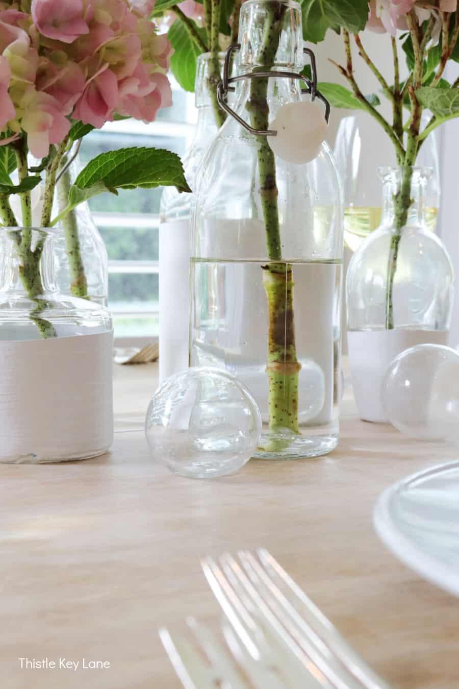 Glass fishing floats arranged around bottle vases. Summer Tablescape With Glass Bottle Vases.