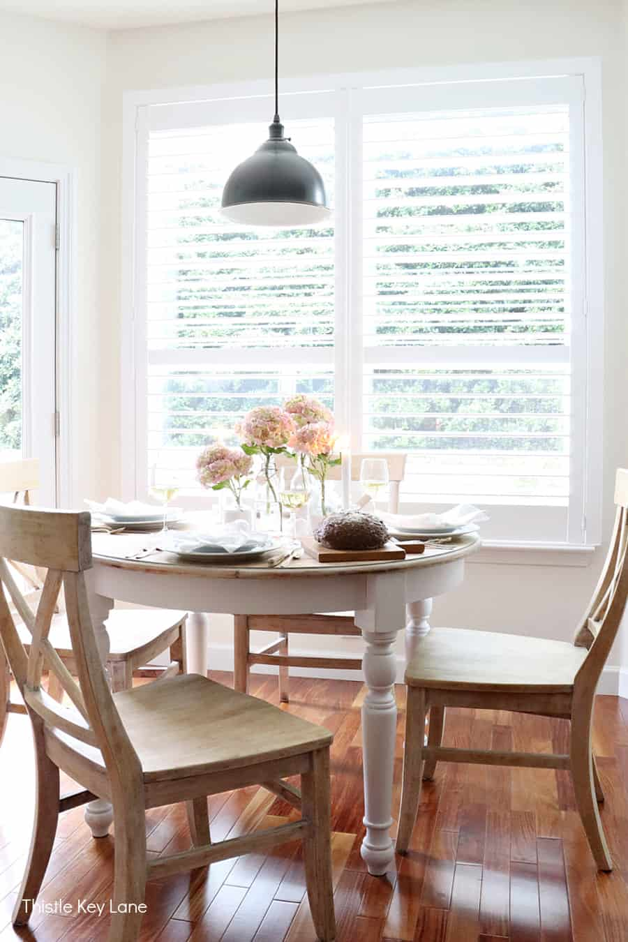 View of table and chair set for summer entertaining. Summer Tablescape With Glass Bottle Vase.
