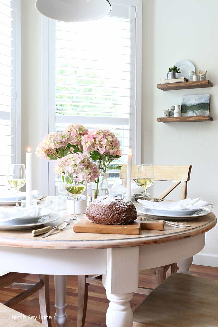 White round table with pink hydrangea flowers in bottles. Summer Tablescape With Glass Bottle Vases.