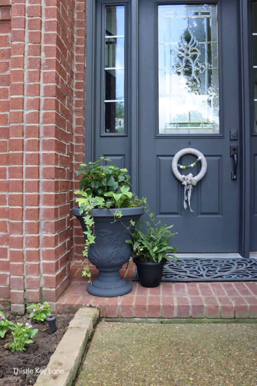 Containers of plants on brick porch with gray door. Updating A Porch Planter For Spring.