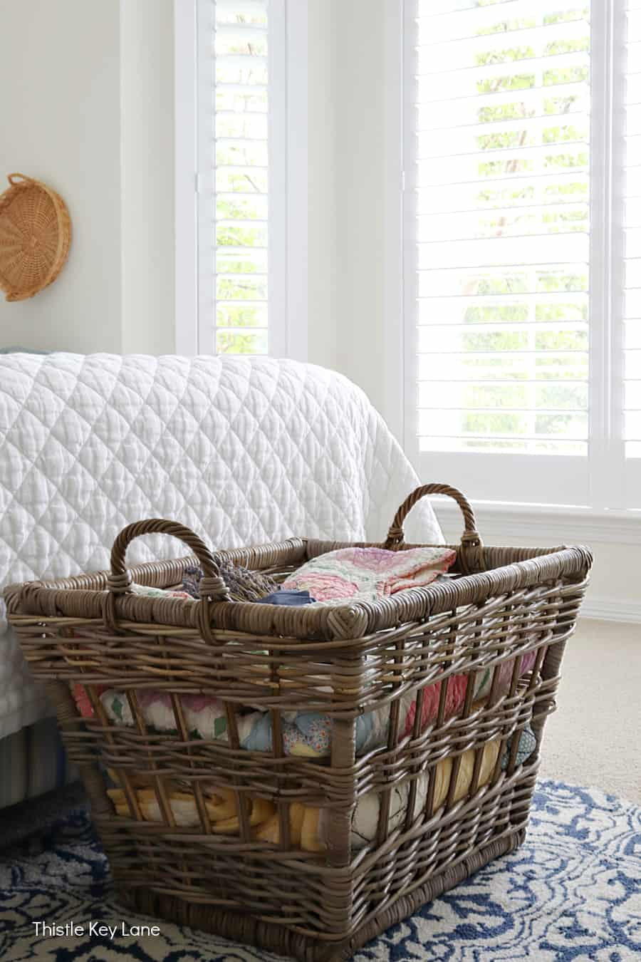 Basket at the foot of the bed with white quilt and big windows. Summer Bedroom Updates And A Quilt Basket.